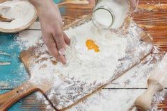 Woman baking. Woman pouring milk into flour as she prepares to bake. Preparing food Royalty Free Stock Photo