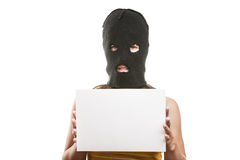 Woman in balaclava holding blank card Stock Photo