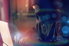 Woman in balaclava using laptop Royalty Free Stock Photography