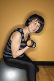 Woman on Balance Ball Lifting Weights Royalty Free Stock Images