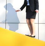 Woman Balances On A Wall. A woman in suit balances on a yellow wall Royalty Free Stock Photo