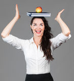 Woman balancing apple and books on head. A happy beautiful business woman balancing books and an apple on her head Stock Photography
