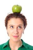 Woman balancing apple on head stock photos