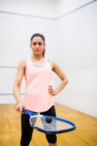 Woman balancing a ball on her racket. In the squash court Stock Photo