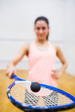 Woman balancing a ball on her racket. In the squash court Royalty Free Stock Photography