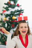 Woman balancing Christmas present box on head Royalty Free Stock Image