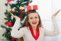 Woman balancing Christmas present box on head Royalty Free Stock Photography