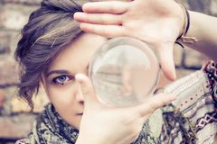 Woman balancing crystal ball. Portrait of young beautiful girl with blue eyes balancing a crystal ball on the hand - Woman performing contact juggling Stock Photos