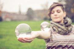 Woman balancing crystal ball Stock Photography