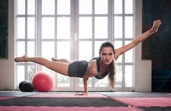 Woman balancing while doing a one hand push up showing strength. And determination Royalty Free Stock Photos