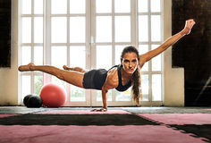 Woman balancing while doing a one hand push up showing strength royalty free stock image