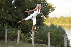Woman balancing on fence post. Attractive blond woman wearing white t-shirt and shorts balancing with one foot on top of a fence post beside a river Stock Photo