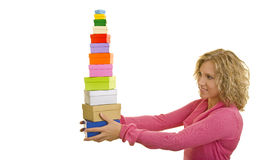 Woman balancing gift boxes. Attractive young blond woman balancing stack of colorful gift boxes, white background stock photography