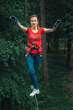 Woman balancing on high in forest adventure rope park. Happy woman climbing between trees on high in adventure rope park in mountain safety equipment Royalty Free Stock Image