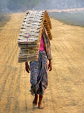 Woman balancing materials. Burma (Myanmar) Woman carrying Roof Materials stock photo