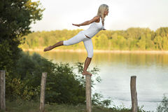Woman balancing beside river. Young blond woman wearing white shorts and vest balancing on one foot on top of post beside river Stock Image