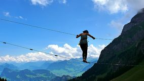 Woman balancing on a rope in the climbing park with a view of the Alps royalty free stock photography