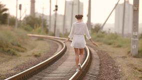 Woman balancing on train rail. Beauty, freedom, summer travel concept. stock footage