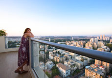 Woman on a balcony in downtown Stock Photo