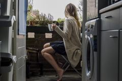 Woman on a balcony drinking a coffee Stock Images