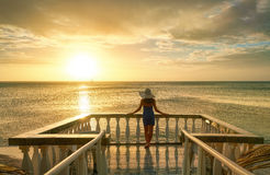 Woman on balcony looking at the beautiful sunset. Stock Images