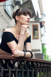 Woman on balcony. Pretty slim young brunette woman model wearing black off-the-shoulder top, elegant earrings, beautiful hairstyle, leaning over the balustrade Stock Images