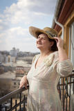 Woman on a balcony, smiles and looks at the sky Stock Photography