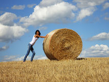 A woman and a bale of hay Stock Images