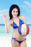 Woman with a ball showing OK sign Royalty Free Stock Photos