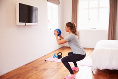 Woman With Ball Working Out To Fitness DVD On TV In Bedroom Stock Photography