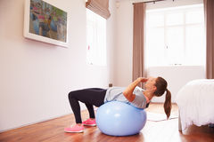 Woman On Ball Working Out To Fitness DVD On TV In Bedroom Royalty Free Stock Image