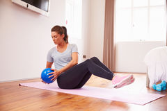 Woman With Ball Working Out To Fitness DVD On TV In Bedroom stock images