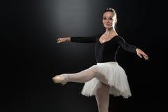 Woman Ballerina Ballet Dancer Dancing On Black Background. Beautiful Female Ballet Dancer On A Black Background - Ballerina Is Wearing A Tutu And Pointe Shoes Stock Images