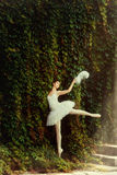 Woman ballerina in a white dress elegantly dances. Woman ballerina in a white dress elegantly dances against the background of foliage in sunlight Stock Image