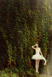 Woman ballerina in a white dress in a park. Woman ballerina in a white dress in a park on a background of green leaves in the sunlight Stock Photos