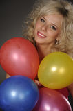 Woman with balloons. Beautiful plump woman playing with balloons on dark background Royalty Free Stock Images
