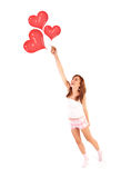 Woman with balloons. Image of cute female flying on red heart-shaped balloons, laughing woman isolated on white background, freedom lifestyle, Valentine day Royalty Free Stock Photography