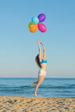 Woman with balloons over sea. Stock Photography