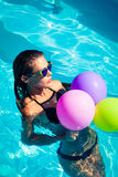 Woman with balloons at pool Stock Photography