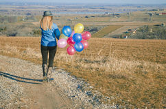 Woman with balloons running away Stock Images