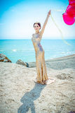 Woman with balloons on the sea. Celebration and lifestyle concept - beautiful woman in gold dress with red balloons on the sea royalty free stock image