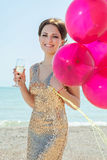 Woman with balloons on the sea. Celebration and lifestyle concept - beautiful happy woman in gold dress with red balloons, glass champagne on the sea stock photos