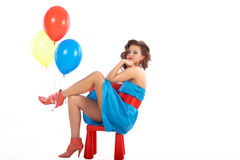 Woman with balloons sitting in a red small chair Royalty Free Stock Photos