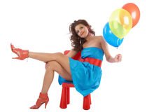 Woman with balloons sitting in a red small chair Royalty Free Stock Photography