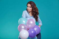 Woman with balloons in studio on a blue background. Woman with balloons in studio Stock Photography