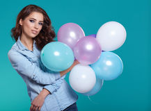 Woman with balloons in studio on a blue background Stock Photos