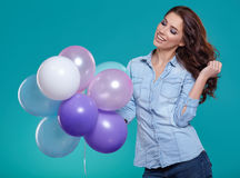 Woman with balloons in studio on a blue background Royalty Free Stock Images
