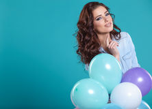 Woman with balloons in studio on a blue background Royalty Free Stock Photos