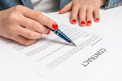 Woman with ballpoint pen signing contract document Stock Photos