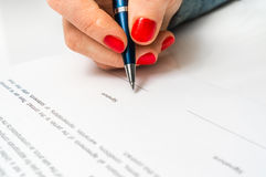 Woman with ballpoint pen signing contract document Stock Photo